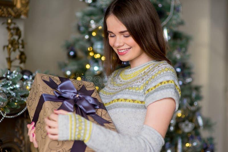 Porträt des attraktiven Mädchens im Pullover, der Geschenkbox hält lizenzfreie stockbilder