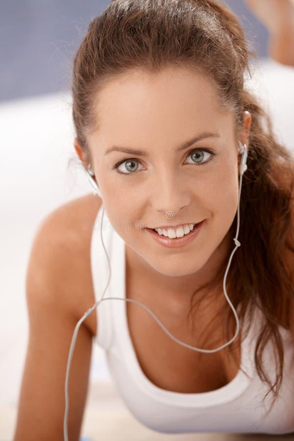 Porträt des attraktiven Mädchens, welches das Kopfhörerlächeln verwendet lizenzfreie stockfotos