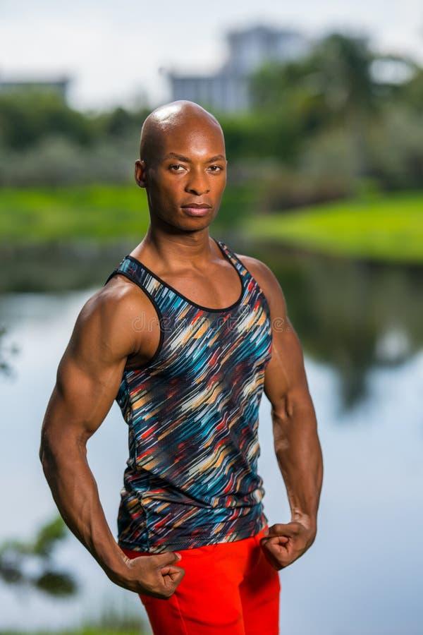 Porträt des attraktiven Mannes seine Arme biegend Das männliche Modell, das draußen in einer Zusammenfassung aufwirft, arbeiten T lizenzfreies stockbild