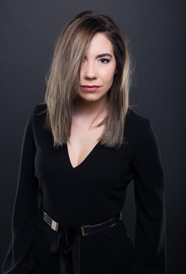 Porträt des attraktiven Modells tragende schwarze Bluse aufwerfend stockfotos