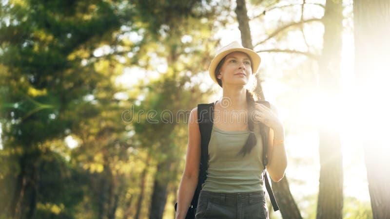 Porträt des attraktiven touristischen Mädchens, das Kamera beim Gehen und Wandern des schönen Waldes lächelt und untersucht stockfotos