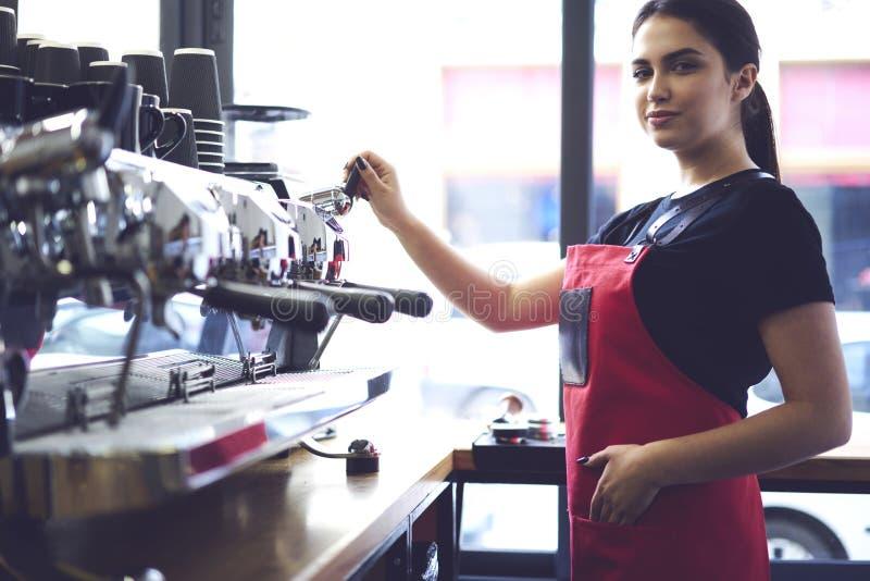 Porträt des attraktiven weiblichen barista, das in der Cafeteria arbeitet stockfotografie