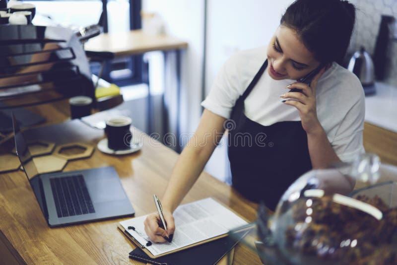 Porträt des attraktiven weiblichen barista, das in der Cafeteria arbeitet lizenzfreie stockfotografie