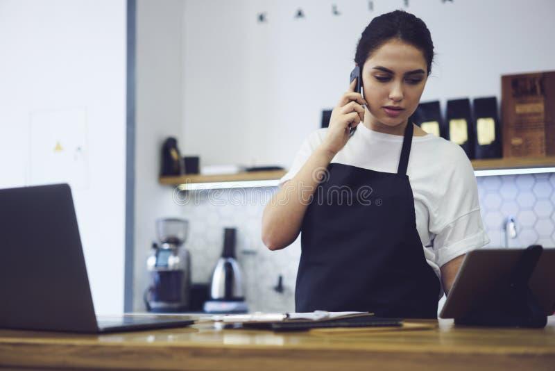 Porträt des attraktiven weiblichen barista, das in der Cafeteria arbeitet stockfoto