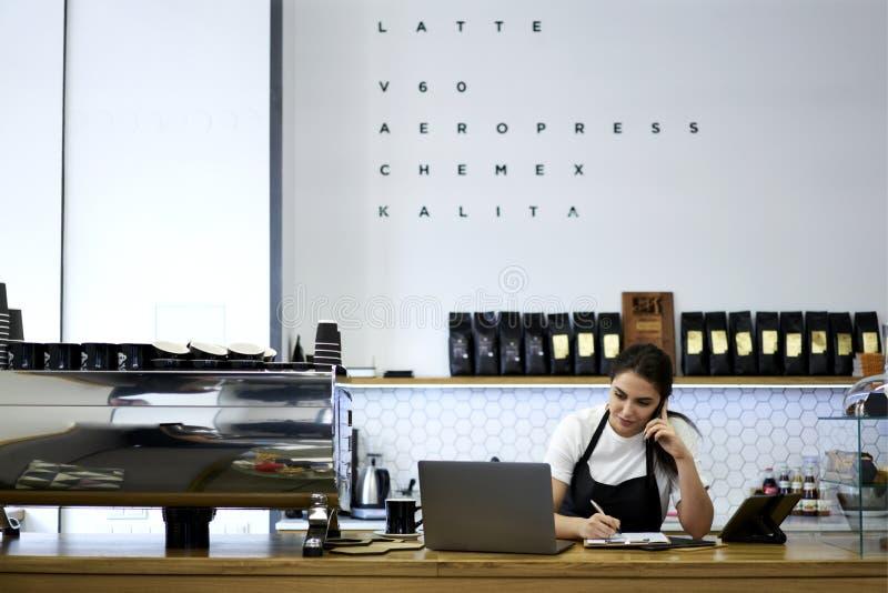 Porträt des attraktiven weiblichen barista, das in der Cafeteria arbeitet stockbild