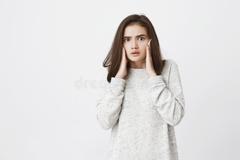 Porträt des attraktiven zarten Mädchens, fassungslos und entsetzt von, was sie sieht, Händchenhalten auf Gesicht mit halb-geöffne stockfotografie