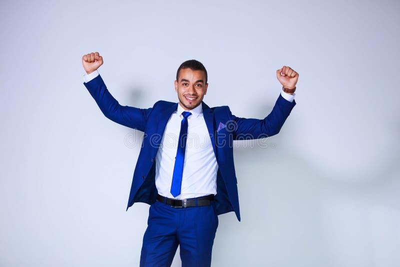 Porträt des aufgeregten glücklichen jungen Geschäftsmannes mit angehobenem Arme sta lizenzfreie stockfotos