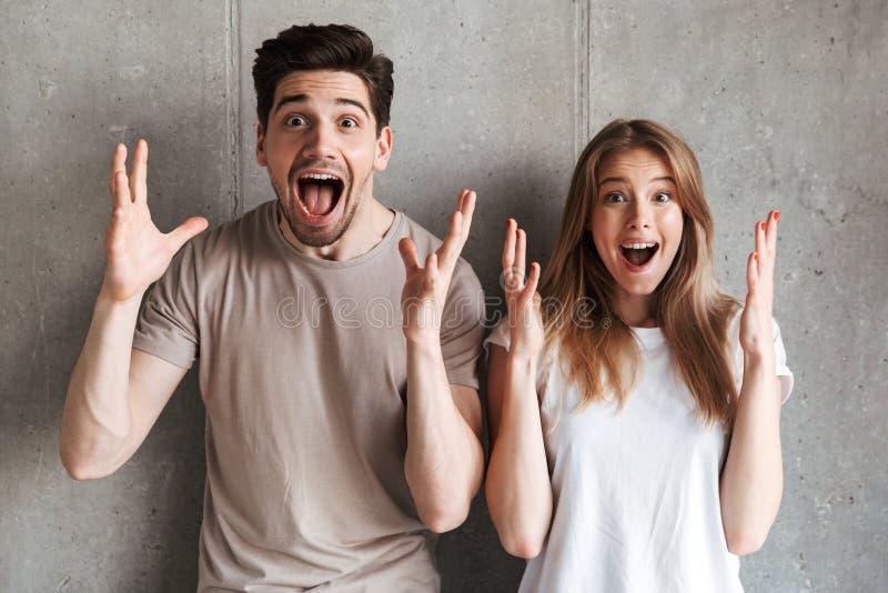 Porträt des aufgeregten Leutemannes und Frau in der grundlegenden Kleidung schreien lizenzfreie stockfotos
