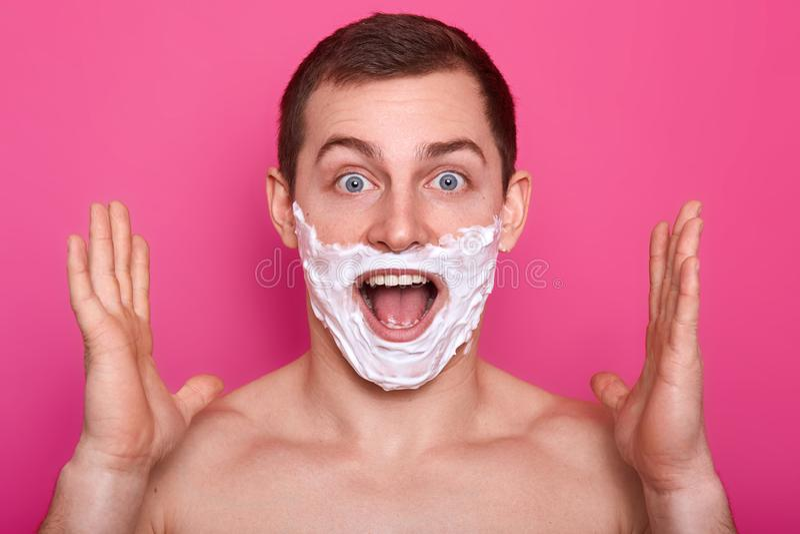 Porträt des aufgeregten Mannes mit Schaum auf seinem Gesicht Überraschter Kerl lokalisiert über rosafarbenem Hintergrund mit Rasi stockfotos