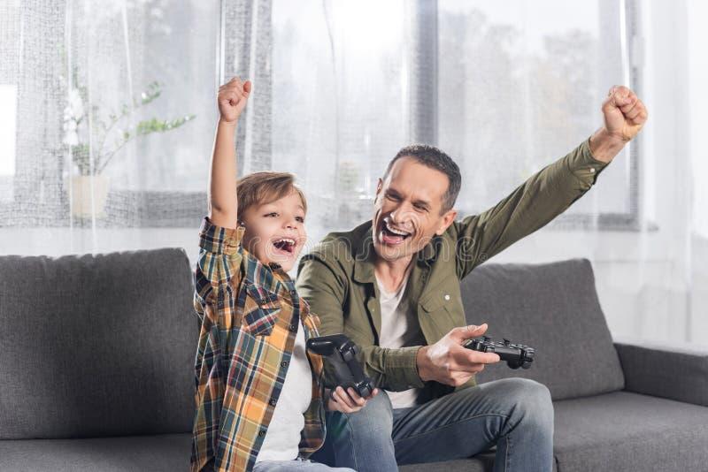 Porträt des aufgeregten Vaters und des Sohns, die zusammen Videospiel spielt stockfotos