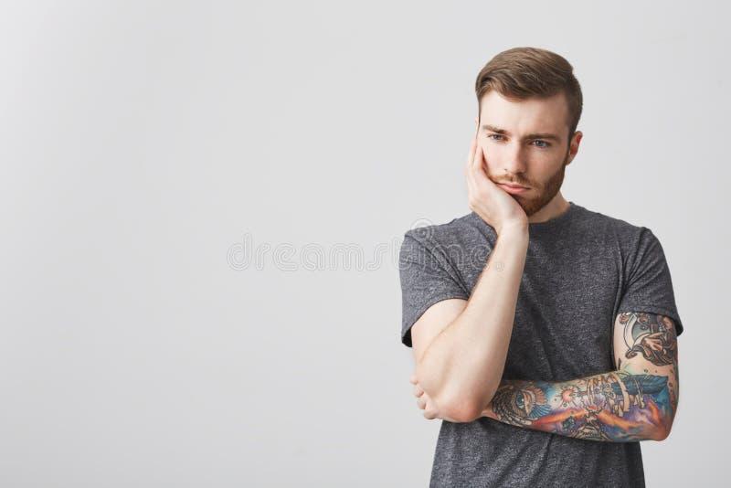 Porträt des bärtigen gutaussehenden Mannes mit stilvoller Frisur und des tätowierten Armholdingkopfes mit der Hand, die beiseite  stockfotografie