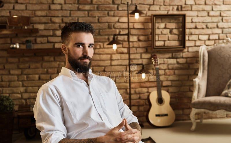 Porträt des bärtigen Mannes am Dachbodenhaus mit Gitarre stockfoto