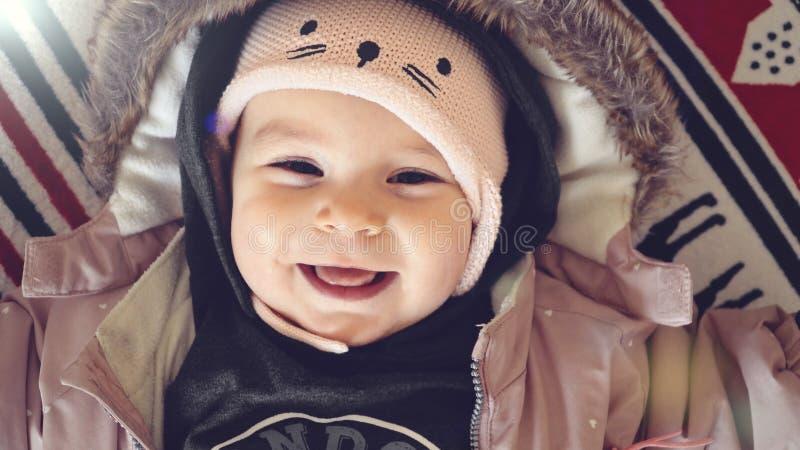 Porträt des Babys in der Winterjacke und -hut lächelnd auf Weihnachtshintergrundausstattungs-Modekleidung lizenzfreies stockbild