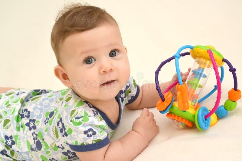 Porträt des Babys mit einem Spielzeug auf einem hellen Hintergrund stockbilder
