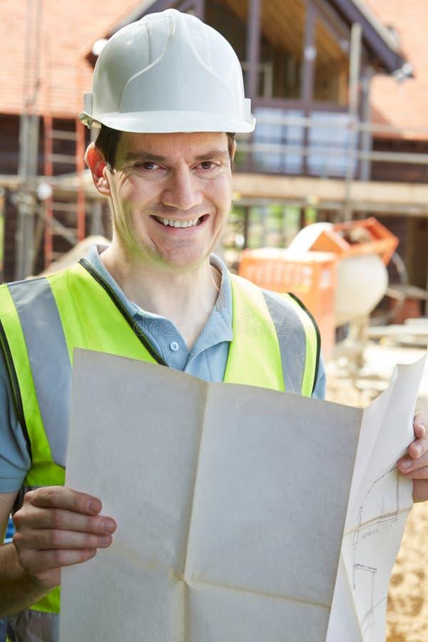 Porträt des Bauarbeiters auf der Baustelle, die Haus-Pläne betrachtet lizenzfreies stockbild