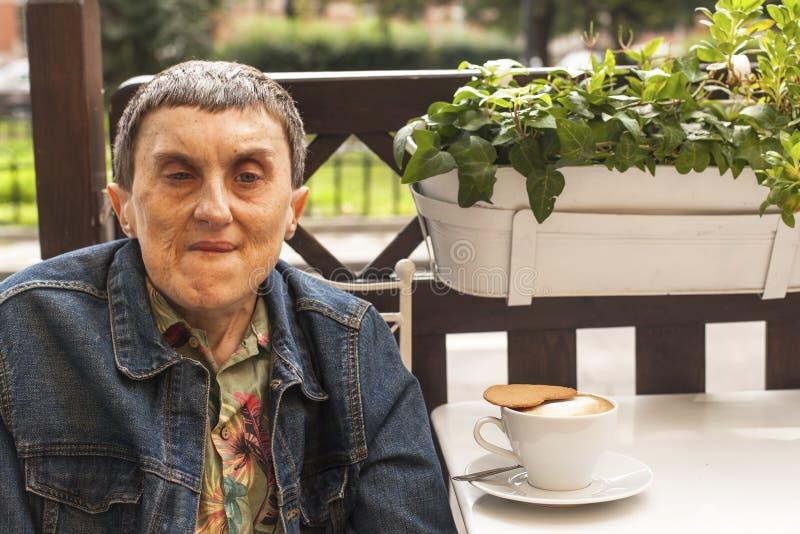 Porträt des behinderten Mannes mit der Zerebralparese, die Café am im Freien mit a des Kaffees sitzt lizenzfreie stockfotos