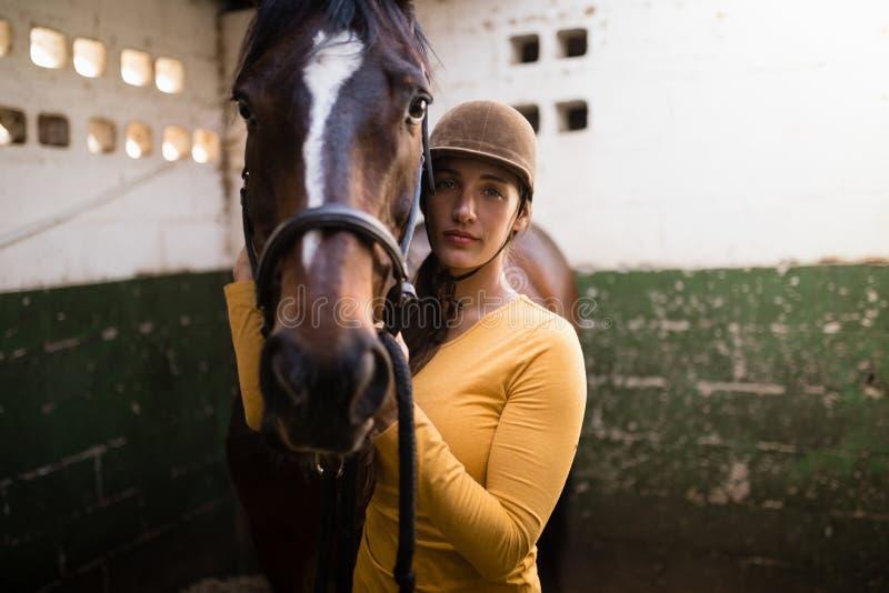 Porträt des bereitstehenden Pferds des weiblichen Jockeys lizenzfreies stockfoto