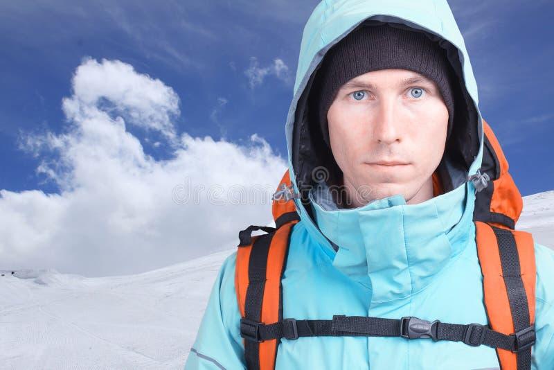 Porträt des Bergsteigers des jungen Mannes in den Winterbergen Blauer Himmel und weiße Wolken stockbilder