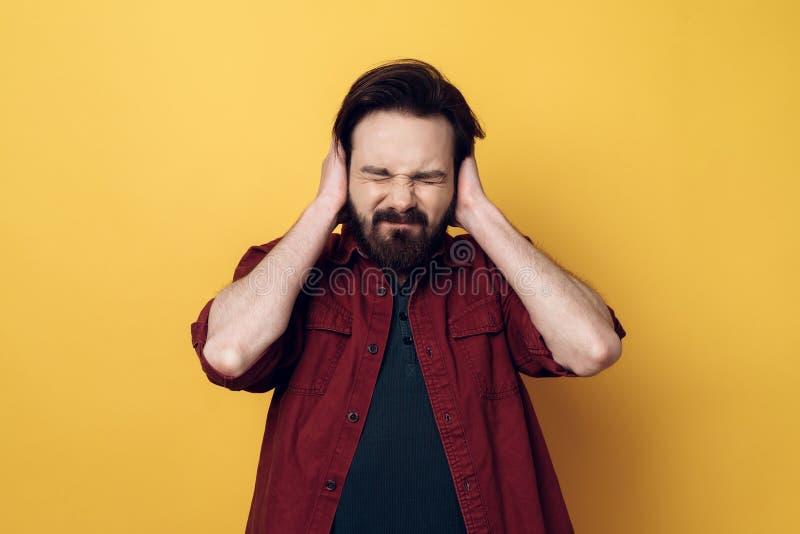 Porträt des beteiligten attraktiven Mannes, der Ohren bedeckt stockbilder