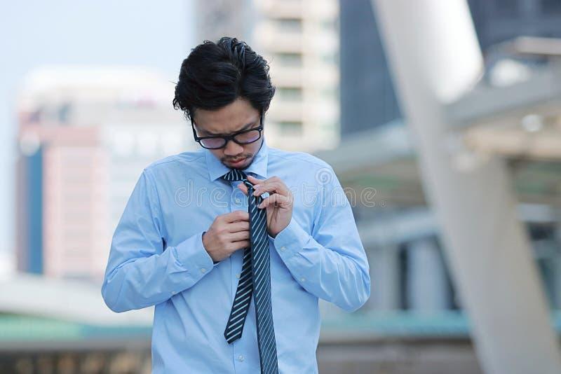 Porträt des betonten jungen asiatischen Geschäftsmannes, der die Bindung auf städtischem Gebäude im Stadthintergrund bindet stockfotos