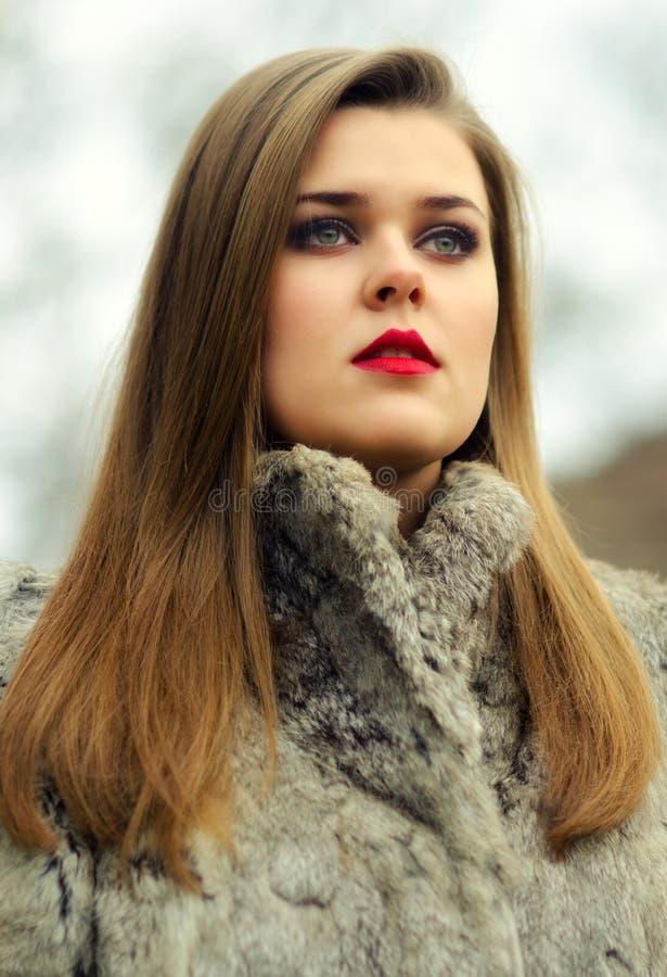 Porträt des bezaubernden Brunette im Pelzmantel stockbilder