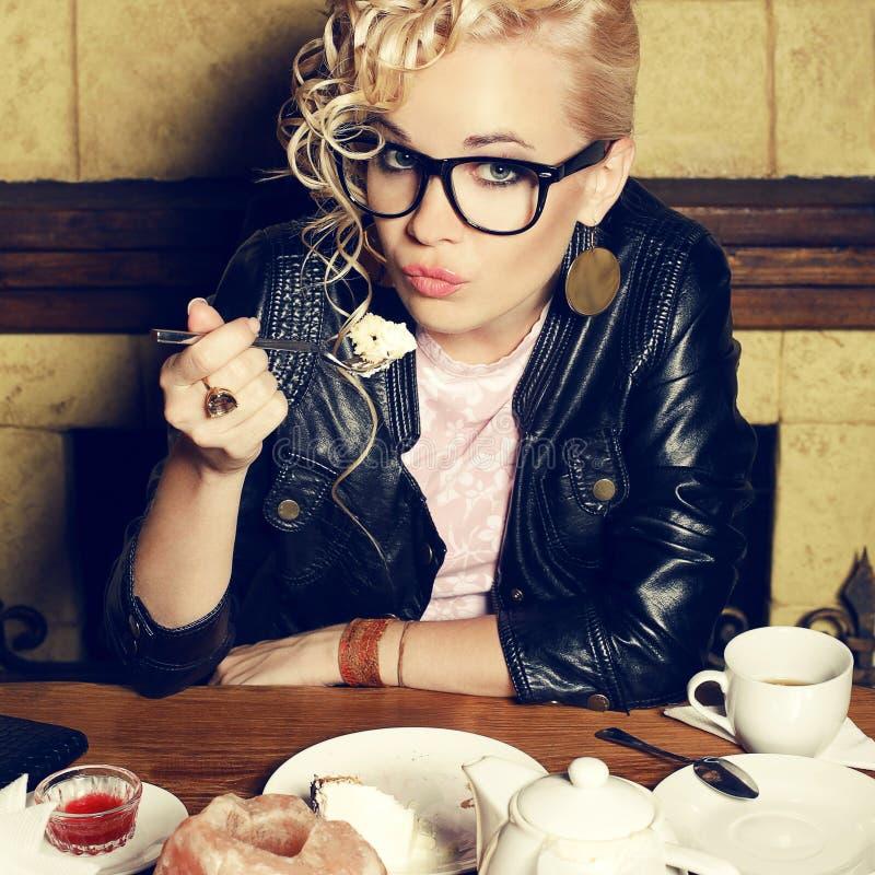 Porträt des blonden Mädchens des lustigen Hippies, das Kuchen isst stockfotos