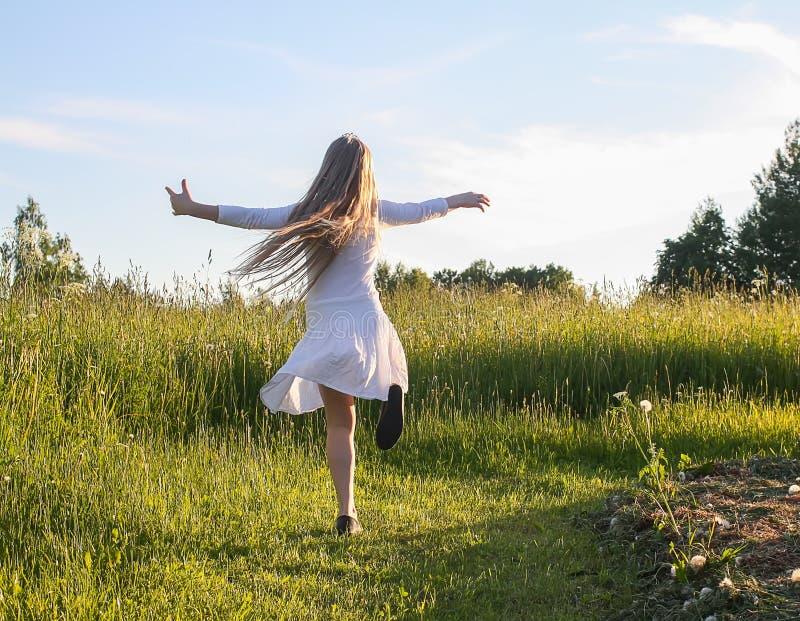 Porträt des blonden Mädchens kleidete im weißen Spielen im Sommerpark an stockfotografie