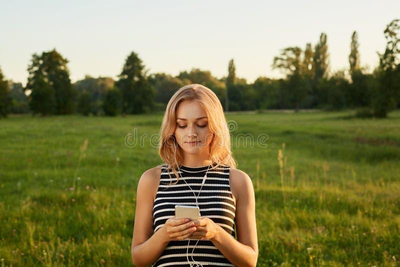 Porträt des blonden Mädchens mit ihrem Handy und Kopfhörern lizenzfreie stockbilder