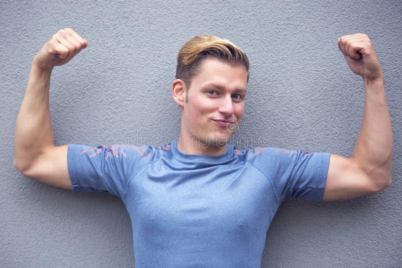 Porträt des blonden Sportlers seine Muskeln vorführend lizenzfreie stockbilder