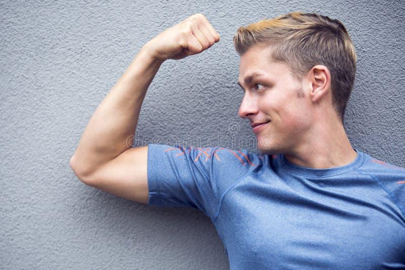 Porträt des blonden Sportlers seine Muskeln zeigend stockbild
