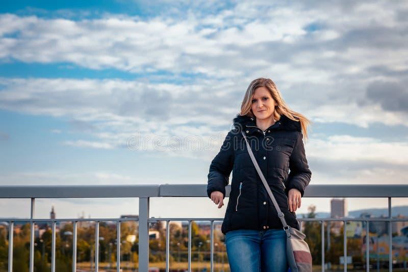 Porträt des blonden Stands der jungen Frau der Schönheit in der Jacke mit Stadt Ceske Budejovice im bacground stockfotos