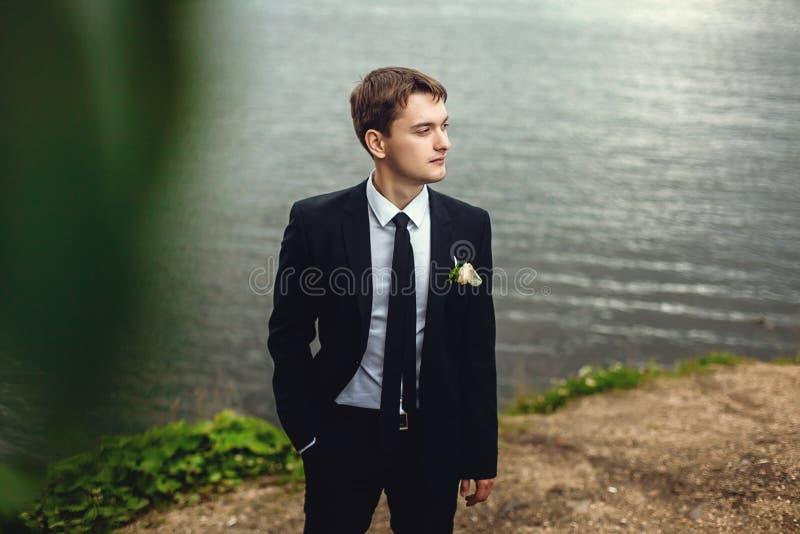 Porträt des Bräutigams in der Natur im Sommer Ein gut aussehender Mann in einer Klage steht auf dem Ufer des Teichs und untersuch stockfoto
