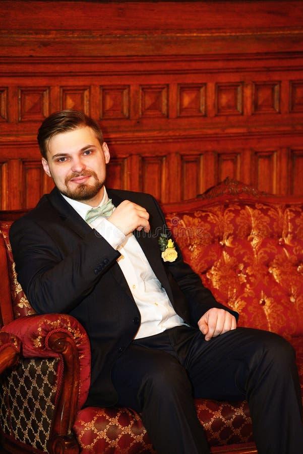 Porträt des Bräutigams sitzend auf Sofa lizenzfreie stockbilder