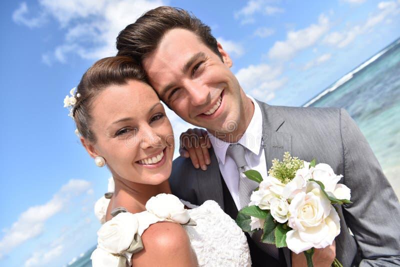 Porträt des Bräutigams und der Braut auf karibischem Strand stockfotografie