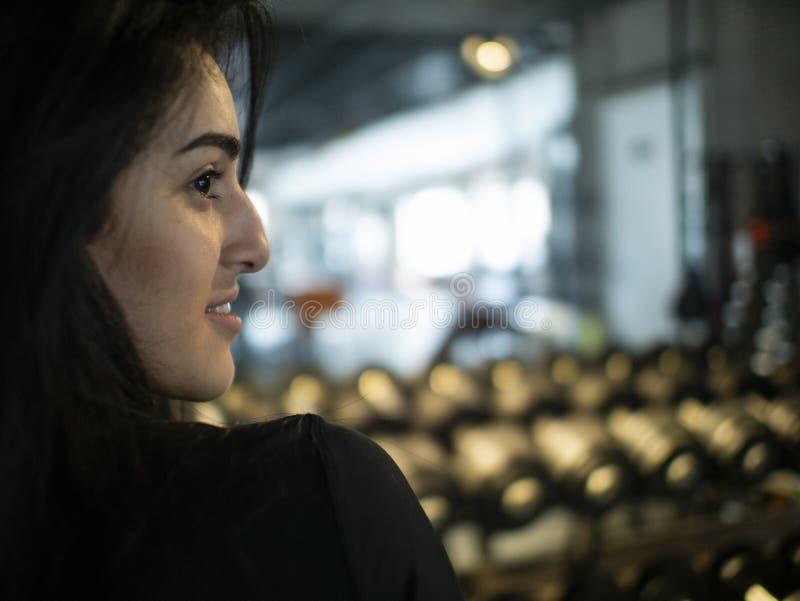Porträt des brunette Mädchens auf einem Hintergrund von Spiegeln und von Regalen mit Dummköpfen in der Turnhalle lizenzfreies stockbild