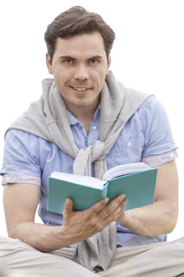 Porträt des Buches des jungen Mannes Lesegegen Himmel lizenzfreie stockfotografie