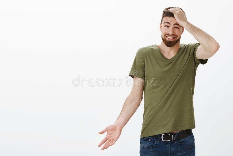 Porträt des charismatischen hübschen bärtigen Mannes, der für Sein spät, vergessend über Zeitholdinghand auf Kopf sich entschuldi lizenzfreies stockfoto