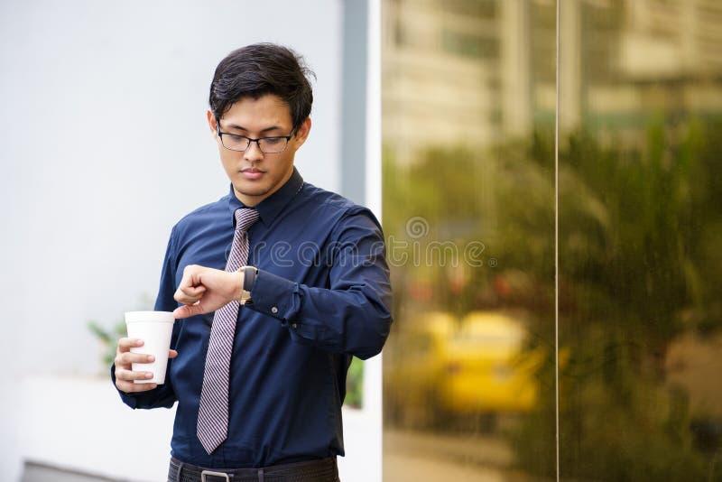 Porträt des chinesischen Büroangestellten, der Zeituhr überprüft lizenzfreie stockfotografie