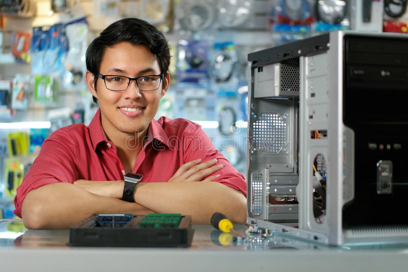 Porträt des chinesischen Mannes mit PC im Computer-Shop lizenzfreie stockbilder