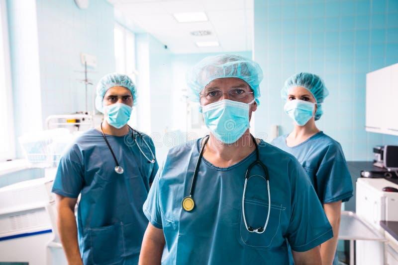 Porträt des Chirurgen und der Krankenschwestern, die im Krankenhaus stehen lizenzfreies stockfoto