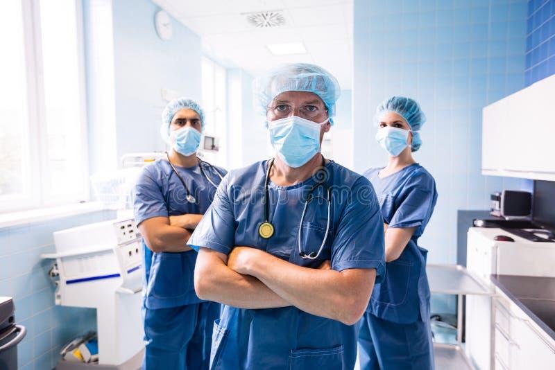 Porträt des Chirurgen und der Krankenschwestern, die im Krankenhaus stehen stockbilder