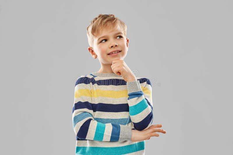 Porträt des denkenden Jungen in gestreiftem Pullover lizenzfreie stockbilder