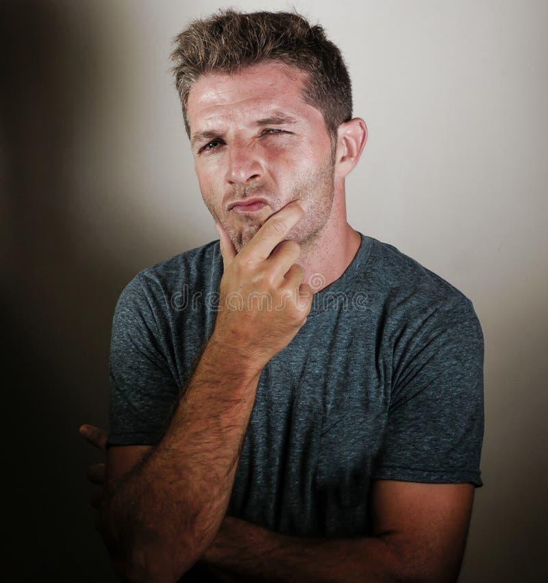 Porträt des denkenden Schauens des jungen attraktiven durchdachten Mannes nachdenklich und zweifelhaft, als ob erwägend oder vers lizenzfreie stockbilder