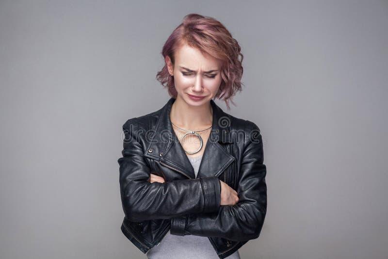Porträt des deprimierten schönen Mädchens mit Kurzhaarfrisur und Make-up in der schwarzen Lederjackestellung der zufälligen Art,  stockfoto