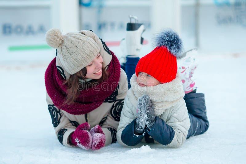 Porträt des Eislaufs des kleinen entzückenden Mädchens und der jungen Frau stockfotografie