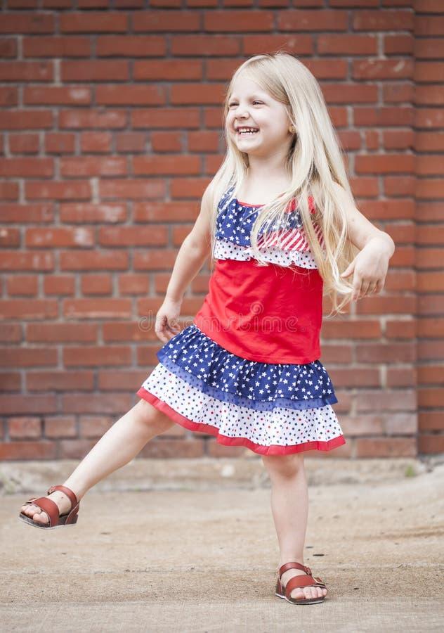Porträt des ekstatischen kleinen Mädchens, das draußen Spaß macht stockbild