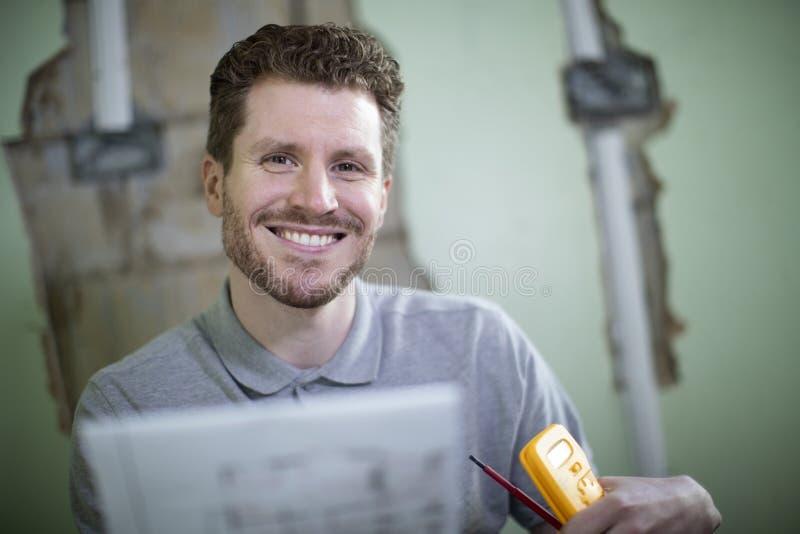 Porträt des Elektrikers Inside House Being erneuerte das Studieren von Plänen lizenzfreies stockfoto