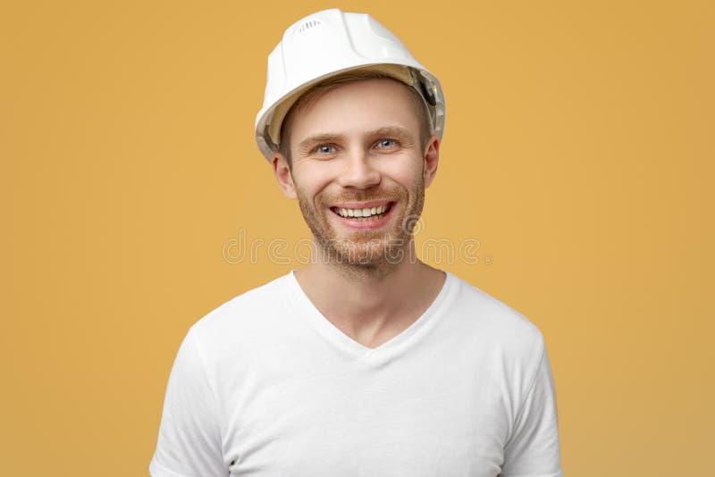 Porträt des enthusiastischen Mannes, lächelt breit, Lachen froh am lustigen Gerücht, trägt Arbeitskleidung mit einem Sturzhelm stockfotografie