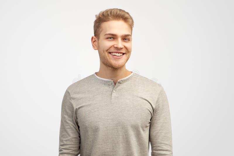 Porträt des enthusiastischen Mannes, lächelt breit, Lachen froh am lustigen Gerücht, trägt zufällige Kleidung lizenzfreies stockfoto