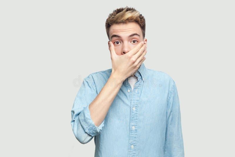 Portr?t des entsetzten h?bschen jungen Mannes in der hellblauen Hemdstellung mit erschrockenem Gesicht, seinen Mund bedeckend und lizenzfreies stockfoto